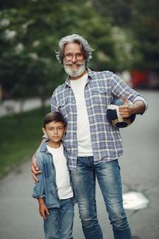 Мальчик и дедушка гуляют по парку. старик играет с внуком. семья играет с мячом.