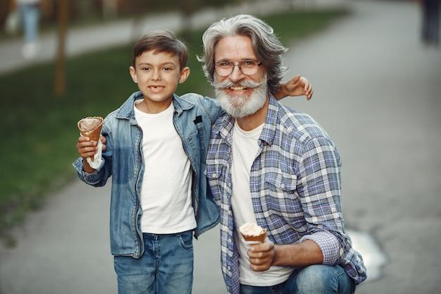 Мальчик и дедушка гуляют по парку. старик играет с внуком. семья с мороженым.