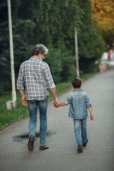 少年と祖父が公園を歩いています。老人が孫と遊んで。