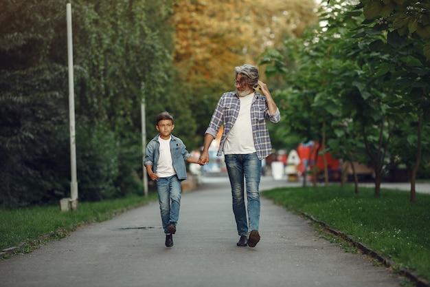 Мальчик и дедушка гуляют по парку. старик играет с внуком.