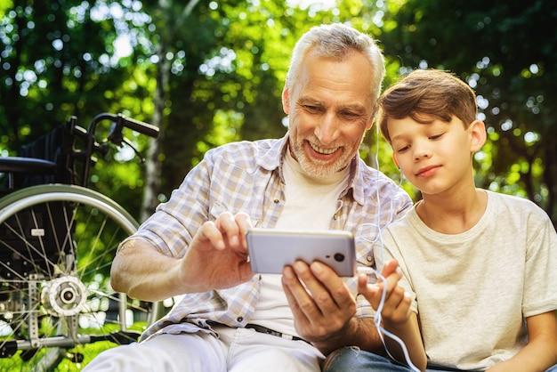 少年と祖父は、スマートフォンを保持します。家族のピクニック。