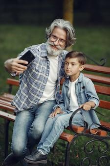 Мальчик и дедушка сидят на скамейке. семья в парке. старик играет с внуком. дедушка пользуется телефоном.