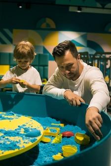 소년과 그의 아빠 C는 다양한 모양을 사용하여 운동 모래로 인물을 만듭니다. 미세 운동 기술의 개발. 미술치료. 창의력과 자가 치유. 상호 이해와 지원. 프리미엄 사진