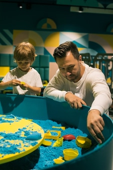 소년과 그의 아빠 c는 다양한 모양을 사용하여 운동 모래로 인물을 만듭니다. 미세 운동 기술의 개발. 미술치료. 창의력과 자가 치유. 상호 이해와 지원.