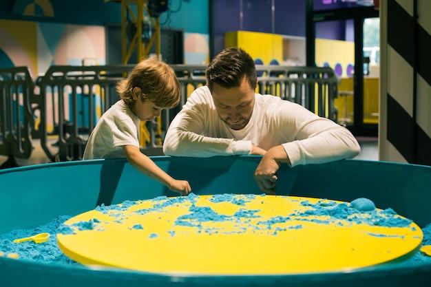 소년과 그의 아버지는 게임 센터에서 색색의 키네틱 샌드를 가지고 열정적으로 놀고 있습니다. 모래 요법. 창의력과 휴식. 부모의 사랑 . 어린이 발달 센터즐거운 감정.