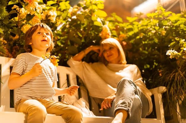 Мальчик и его мама сидят на скамейке в городском парке, сын и мать веселятся на бревенчатом сиденье с кустами