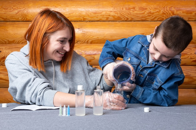 소년과 그의 어머니, 과학자들은 집에서 실험하기 위해 화학 원소가 든 병에 물을 붓습니다.