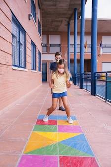 少年と少女は、covidパンデミックの最中にフェイスマスクを持って校庭を走ったりジャンプしたりします。