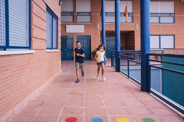 コビッドパンデミック時にフェイスマスクを持って校庭を走っている少年と少女。コビッドパンデミック中に学校に戻る