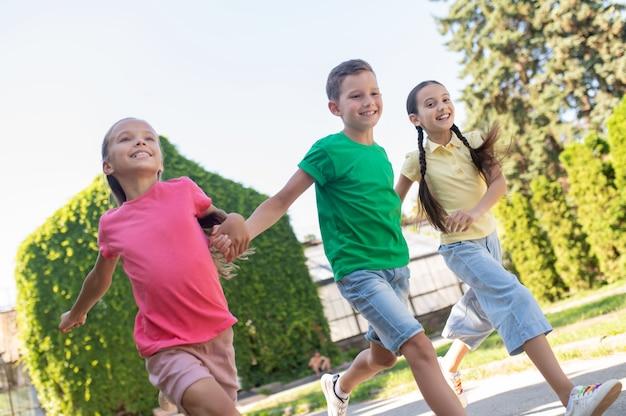 Мальчик и две девочки бегут в парке