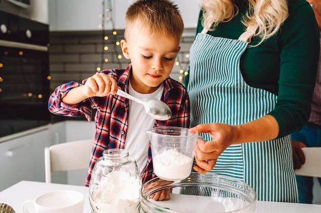 소년과 알 수없는 엄마가 크리스마스 이브에 함께 부엌에서 요리합니다.