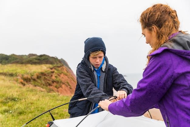 Мальчик и женщина установили палатку на скалах