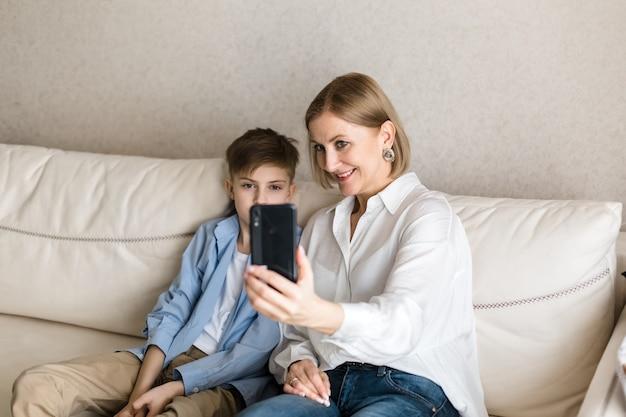 Мальчик и женщина делают селфи по телефону и улыбаются