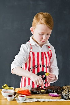 A boy in an apron cooking in the kitchen burger.
