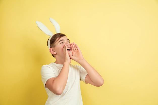 Ragazzo come un coniglietto di pasqua sulla parete gialla dello studio