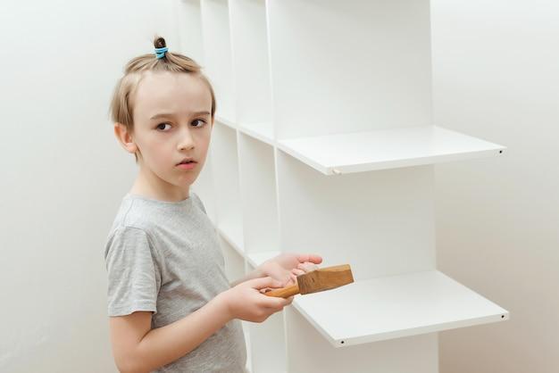 Мальчик сам собирает книжную полку. сын помогает папе собирать дома новую мебель. сборка мебели своими руками.