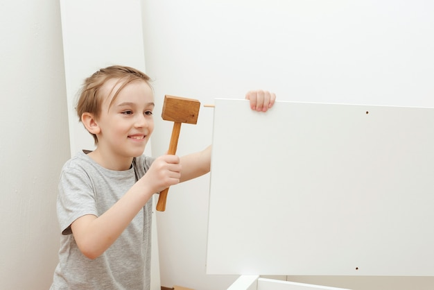 Boy assembles a bookshelf himself. child with hammer. son helping his dad to assembling new furniture at home. furniture assembly yourself. childhood, lifestyle concept.