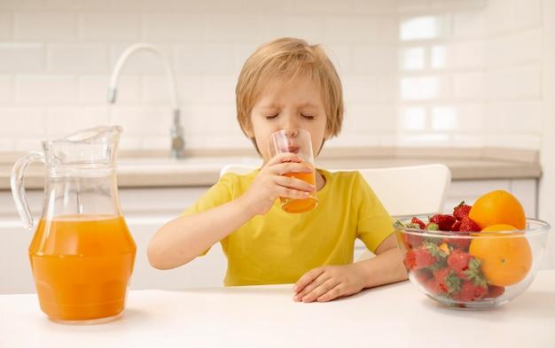 自宅でジュースを飲む少年