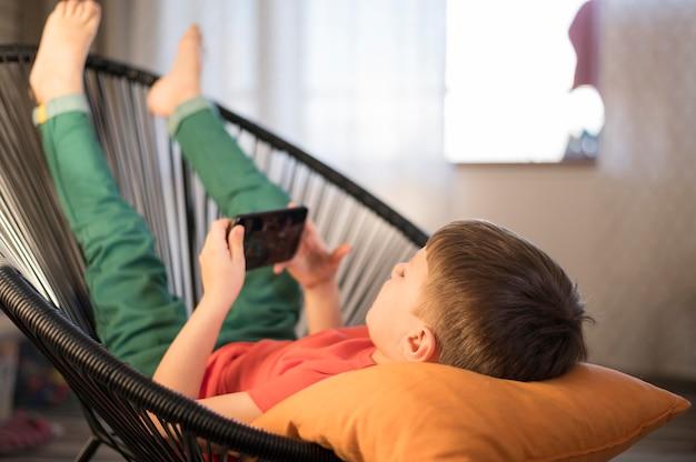 自宅で携帯で遊ぶ少年
