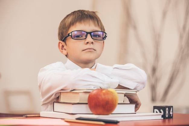 Мальчик в школе, за школьной партой с книгами в очках