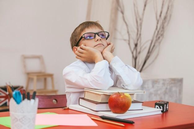 学校の男の子、眼鏡をかけた本を持った学校の机
