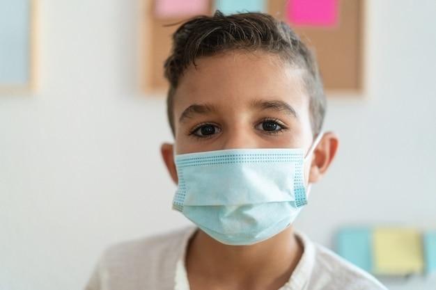 保護マスクを身に着けている学校の少年