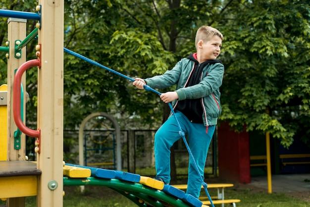 놀이터에서 소년입니다. 로프 경쟁. 올라간다. 여름에 행복한 어린 시절. 성취와 성공을 위해 노력합니다. 야외 놀이터