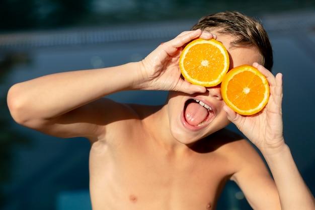 Мальчик у бассейна с цитрусовыми