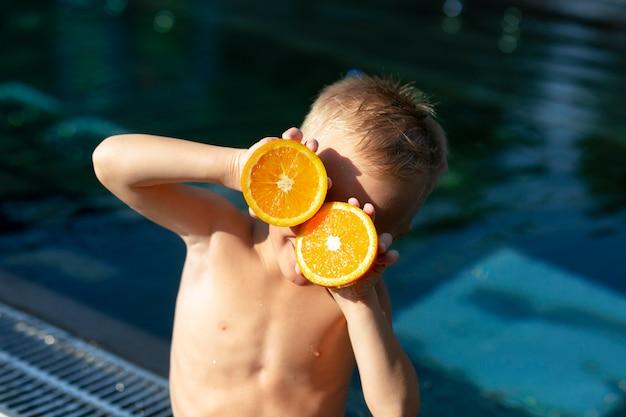 감귤류와 함께 수영장에서 소년