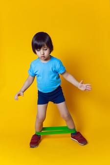 Boy athlete does gymnastics with an elastic band in a sports club on a yellow wall