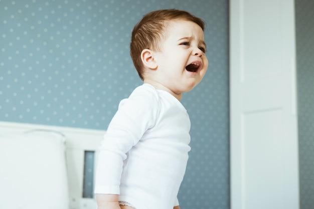 침실에서 우는 소년 아기. 슬프고 화난 아이 초상화 측면 보기