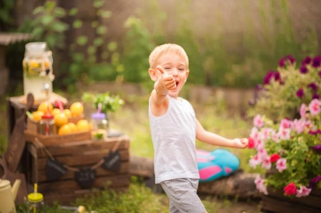 A boy in the backyard sells homemade lemonade and copy space. boy, lemons, lemonade.