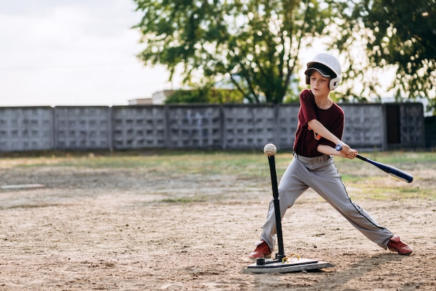 A boy, a baseball player, hits a ball with a baseball bat
