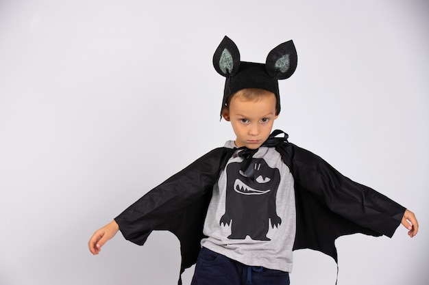 Boy in a bat costume. opening his arms to the side shows his wings. holiday concept. white isolated wall.
