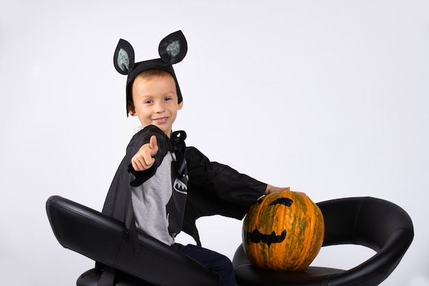 A boy in a bat costume sits on black chairs with a pumpkin. photo on a white wall. ready for the holiday.