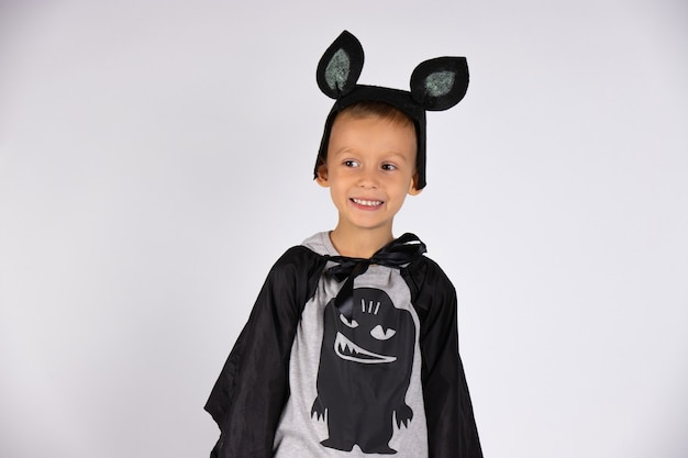 A boy in a bat costume with cute ears, smiles and looks to the side with his eyes. white isolated wall.
