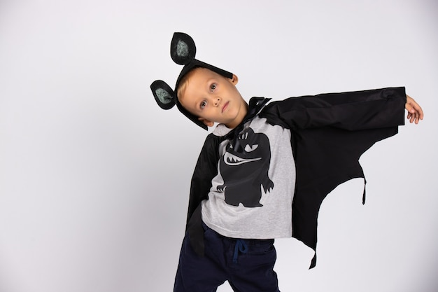 The boy bat is smiling and happy preparing for the holiday. photo on a white wall. happy halloween.