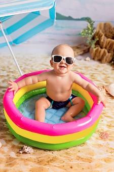 少年は海沿いの砂浜のビーチパラソルの下の膨脹可能なプールで入浴します。