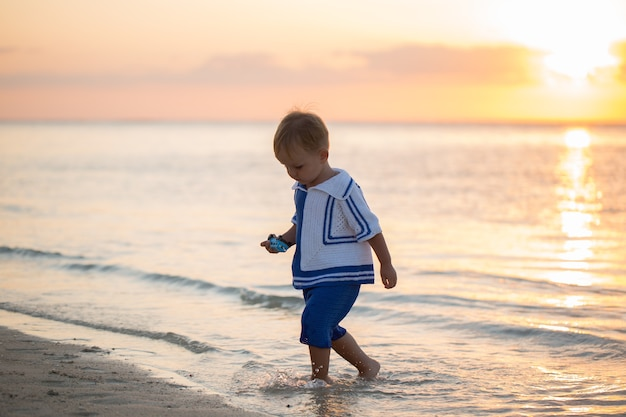 Boy on the beach. wooden boat on the horizon.