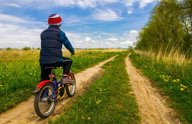 Boy on bike on country road in sunny day