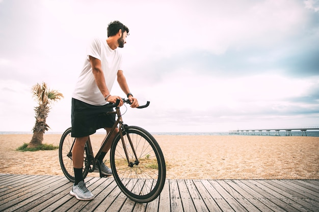 Boy on a bike on a wood walkway on the beach looking at the sea copy space sport  lifestyle