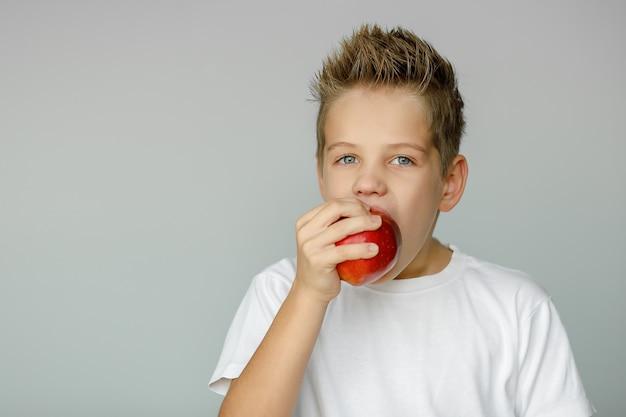 한 손으로 과일을 들고 빨간 사과 물고 소년