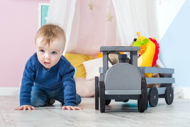 Boy blond in blue sweater crawls on wooden floor one year old baby playing with wooden toys train