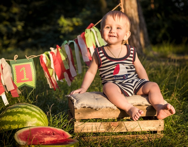 Boy blond sits surrounded by watermelons on a summer day
