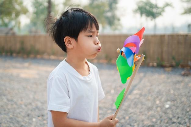 公園で朝におもちゃの風車を吹く少年