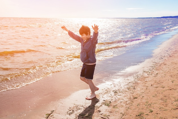 Boy in blue jacket and shorts barefoot joyfully running with hands up on sand on the seashore, sunny day