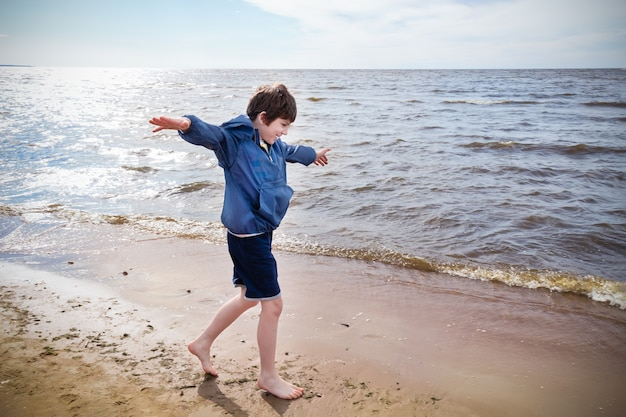 Boy in blue jacket and shorts barefoot running on sand on the seashore, sunny day, vignetted.