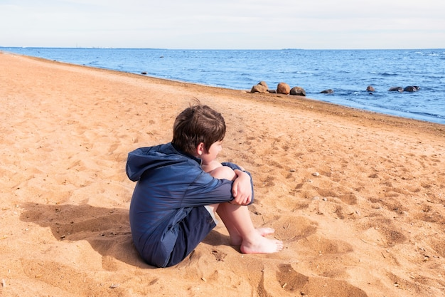 Boy in blue jacket and shorts barefoot sitting on the sand on the seashore, sunny day.