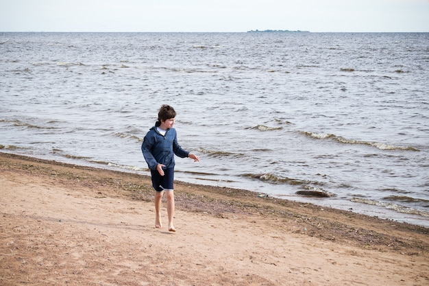 Boy in blue jacket and shorts walking barefoot on sand on seashore in sunny day
