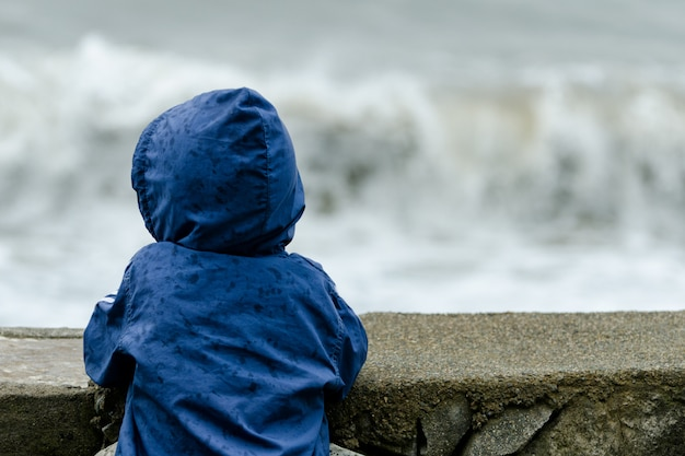 Boy in blue jacket with hood stands with his back. pier against the background of sea waves